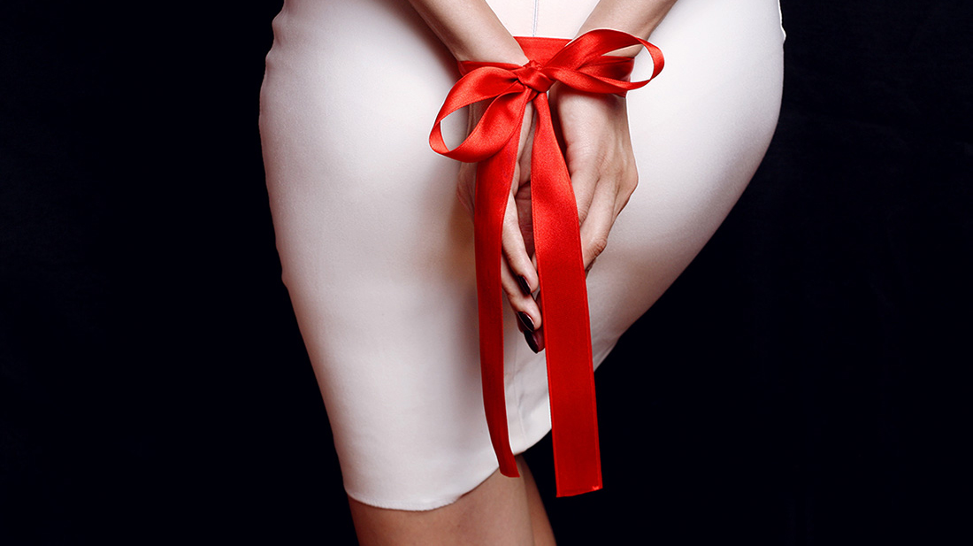 Woman in a white dress shows her hands tied behind her back with a red ribbon in kink play.