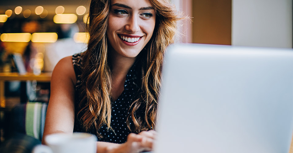 Beautiful smiling woman sits in front of her laptop while she makes an online dating profile