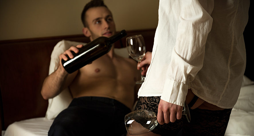 Man lying in bed pouring wine for his affair partner who is wearing his shirt.