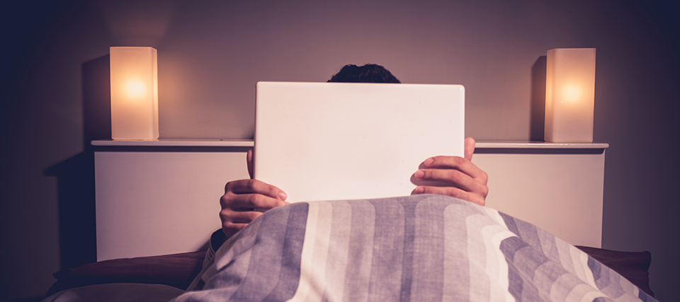 Man is sitting in bed behind his laptop likely watching porn